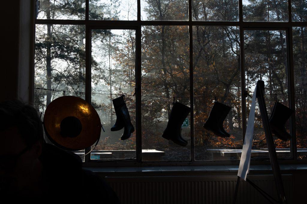 De zon komt langs de bomen door de ramen in de Theaterloods naar binnen